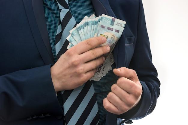 L'uomo d'affari prende un pacco di soldi ucraini come tangente e si nasconde in tasca in una giacca. corruzione e trucco. uah. 1000 nuove banconote