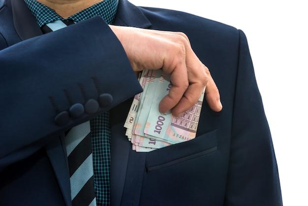 L'uomo d'affari prende un pacchetto di soldi ucraini come una tangente e si nasconde in tasca in una giacca. corruzione e trucco. uah. 1000 banconote nuove