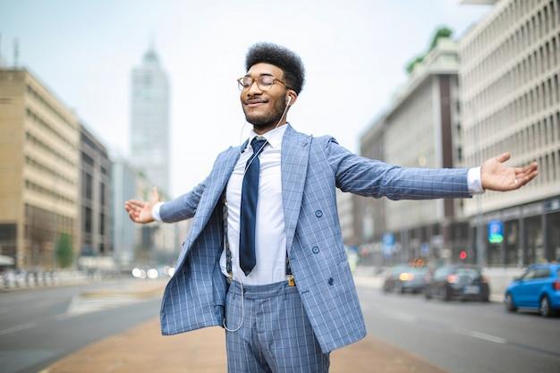 Uomo d'affari che fa un respiro profondo mentre si sveglia in strada