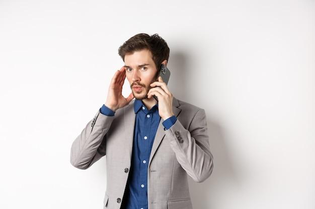 Uomo d'affari che parla al telefono e che copre l'orecchio, riceve una chiamata in un luogo rumoroso, non può sentire il chiamante, in piedi su sfondo bianco