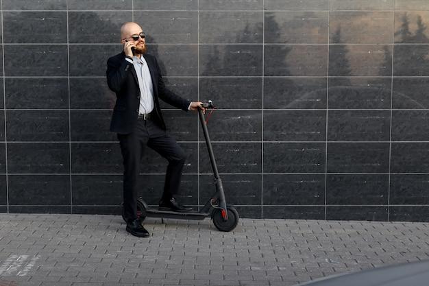 Uomo d'affari che parla al telefono, accanto allo scooter elettrico