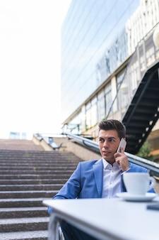 Uomo d'affari parlando al telefono seduto in un caffè. giovane che utilizza il cellulare all'aperto. concetto di affari.