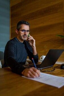 Imprenditore parlando al telefono mentre si scrive su un pezzo di carta a casa