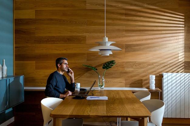 Uomo d'affari parlando al telefono e lavorando sul suo laptop nel suo salotto