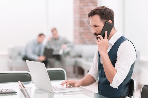 Imprenditore parlando su uno smartphone seduto alla sua scrivania