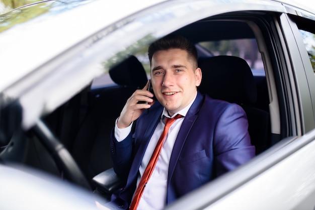Un uomo d'affari parla al telefono in macchina