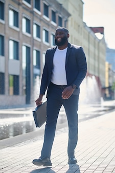 Uomo d'affari. un uomo alto dalla pelle scura in giacca e cravatta per strada