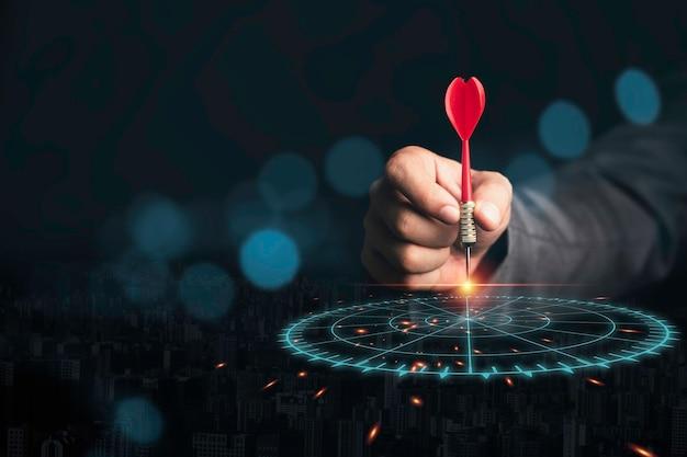 Uomo d'affari che getta il dardo della freccia rossa al bersaglio per le freccette virtuale. impostare obiettivi e target per il concetto di investimento aziendale.