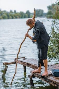 Uomo d'affari in tuta strappata pesca sull'isola deserta. rischio aziendale, crollo o concetto di fallimento