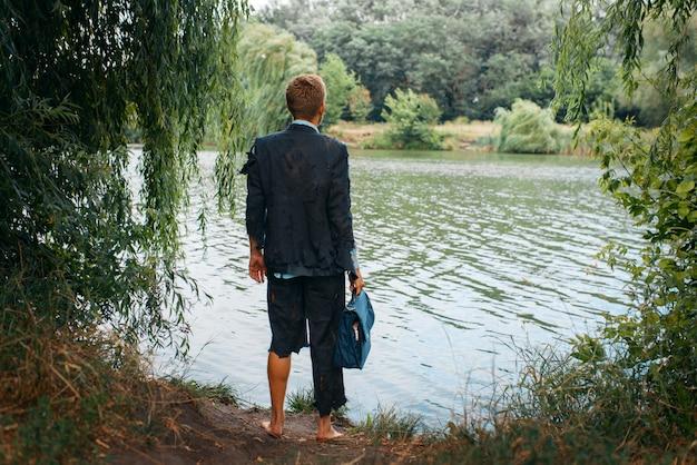 Uomo d'affari in tuta strappata tiene valigetta su un'isola deserta, vista posteriore. rischio aziendale, crollo o concetto di fallimento