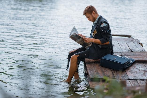 Uomo d'affari in vestito strappato leggendo il giornale su un'isola deserta.