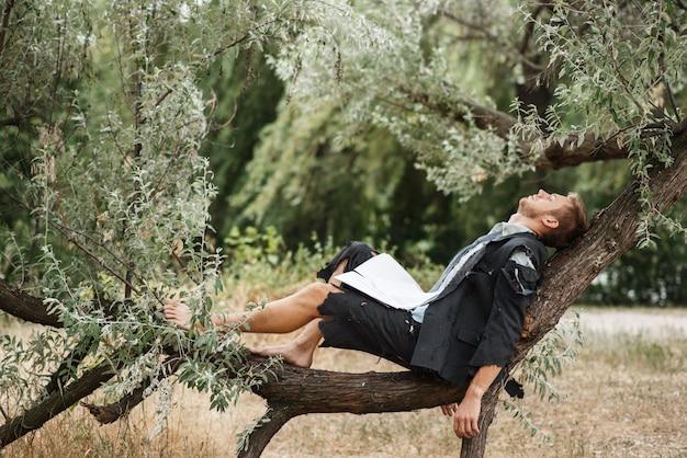 Uomo d'affari in vestito strappato che riposa sull'albero sull'isola deserta. rischio aziendale, crollo o concetto di fallimento