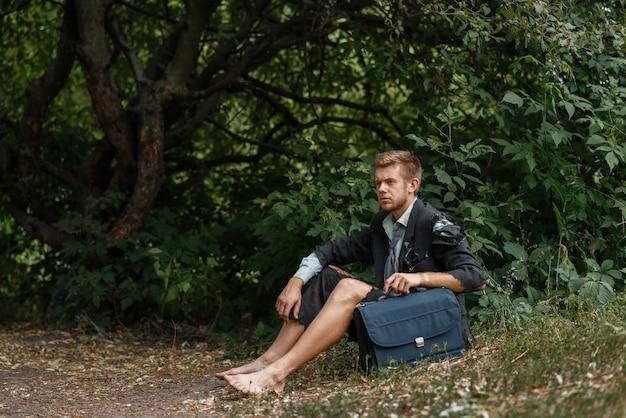 Uomo d'affari in abito strappato seduto per terra su un'isola deserta. rischio aziendale, crollo o concetto di fallimento