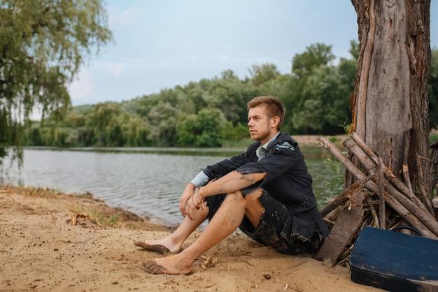 Uomo d'affari in abito strappato seduto sulla sabbia sull'isola perduta. rischio aziendale, crollo o concetto di fallimento