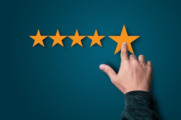 Uomo d'affari che tocca a cinque stelle gialle su sfondo blu scuro, la migliore soddisfazione del cliente e la valutazione per prodotti e servizi di buona qualità.