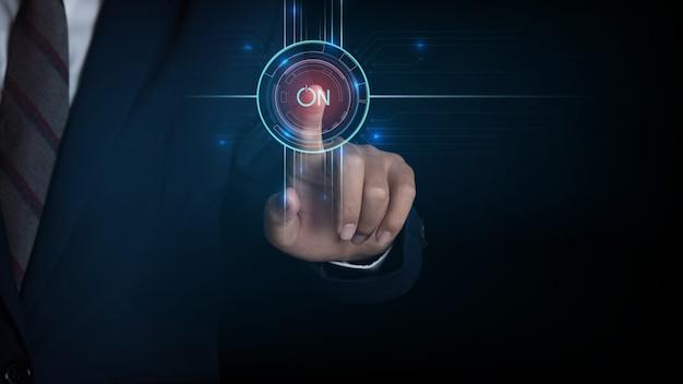 Schermo commovente dell'uomo d'affari, spingente su un pulsante di accensione del touch screen. innovazione di concetto.