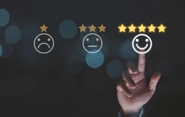 Uomo d'affari che tocca le icone del fronte di sorriso con cinque stelle d'oro su sfondo blu bokeh, soddisfazione del cliente per il concetto di prodotto e servizio.
