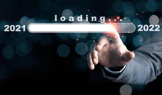 Uomo d'affari che tocca alla barra di download virtuale con caricamento della barra di avanzamento per la vigilia di capodanno e cambia l'anno dal 2021 al 2022.