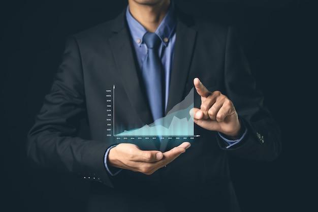 L'uomo d'affari o il commerciante sta mostrando uno stock di ologramma virtuale in crescita, investe nel trading.pianificazione e strategia, concetto di mercato azionario.