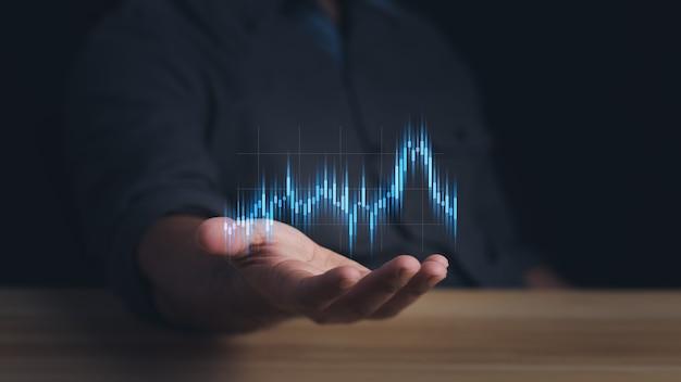 L'uomo d'affari o il commerciante sta mostrando un crescente stock di ologrammi virtuali che investe nel commercio