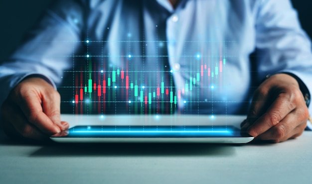 L'uomo d'affari o il commerciante sta mostrando sul tablet un mercato azionario virtuale in crescita con ologramma