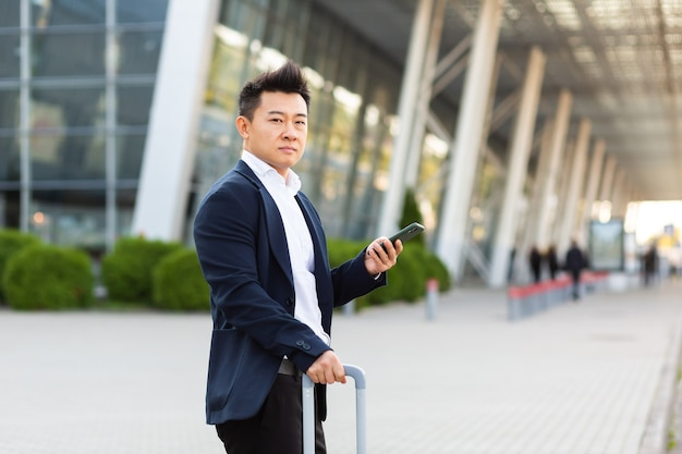 Uomo d'affari che cerca di chiamare un taxi usando un'app e un telefono cellulare, uomo asiatico alla stazione ferroviaria con una grande valigia