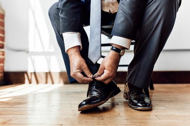 Uomo d'affari che allaccia i lacci delle scarpe prima di andare al lavoro