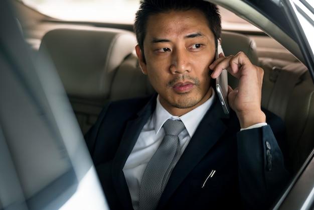 L'uomo d'affari usa l'auto mobile per parlare