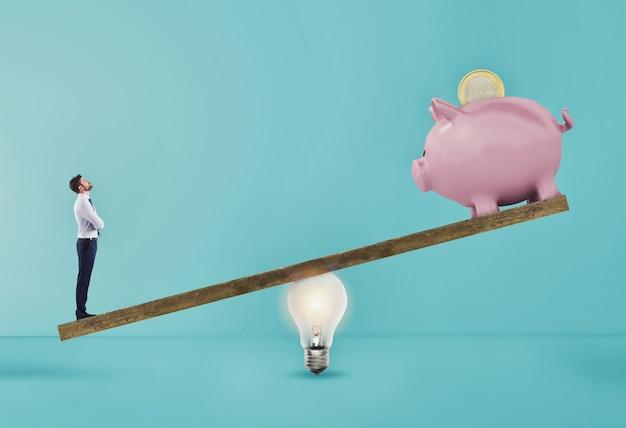 L'uomo d'affari utilizza la leva dell'annuncio della lampadina per sollevare il salvadanaio. concetto di facile guadagno con una buona idea. sfondo ciano