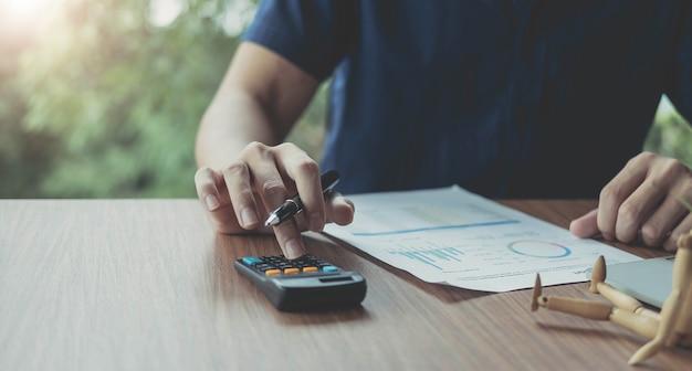 Uomo d'affari che utilizza la calcolatrice per l'analisi del piano di creazione, il contabile calcola il rapporto finanziario, il computer con il grafico concetti di affari, finanza e contabilità
