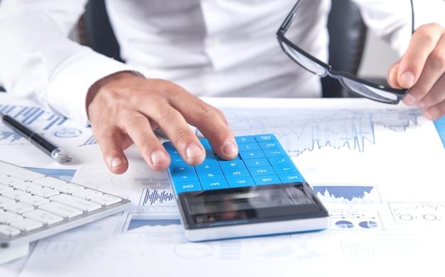 Uomo d'affari che utilizza la calcolatrice per l'analisi del piano di marketing