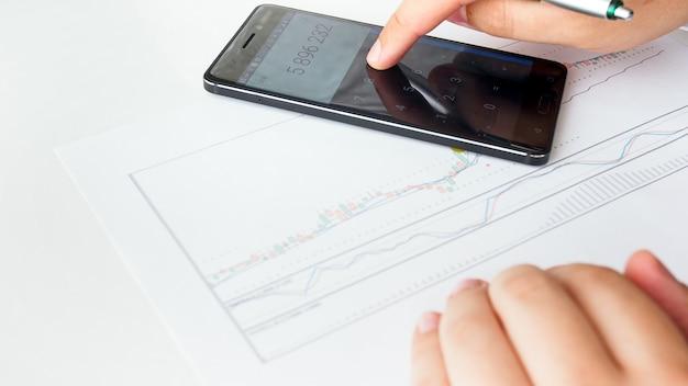 Uomo d'affari che utilizza la calcolatrice durante l'analisi del mercato azionario finanziario