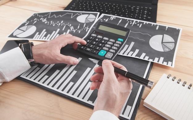 Uomo d'affari utilizzando la calcolatrice. lavorare in grafici finanziari