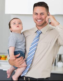 Uomo d'affari che utilizza cellulare mentre portando bambino in casa