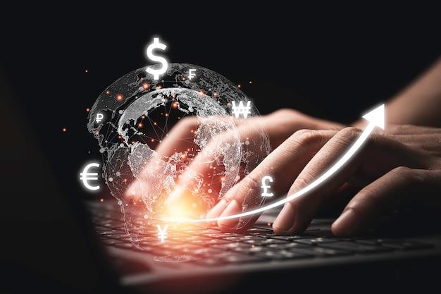 Uomo d'affari che utilizza computer portatile con mondo virtuale con segno di valuta come dollaro yen yuan euro e sterlina per cambio valuta e trader per concetto di tecnologia.