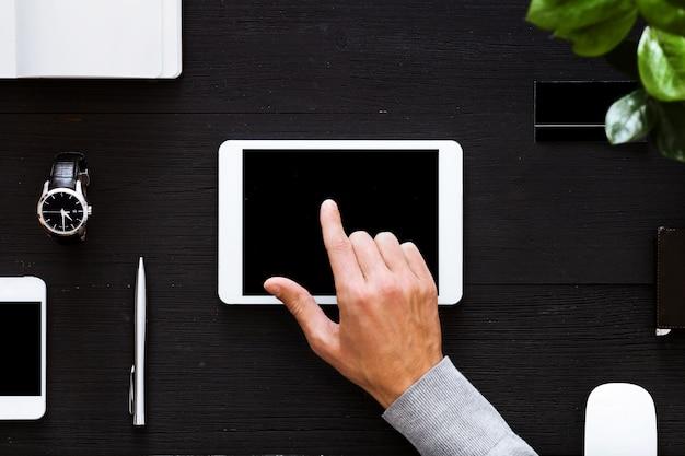 Uomo d'affari facendo uso dello schermo digitale della compressa sulla tavola dell'ufficio di affari