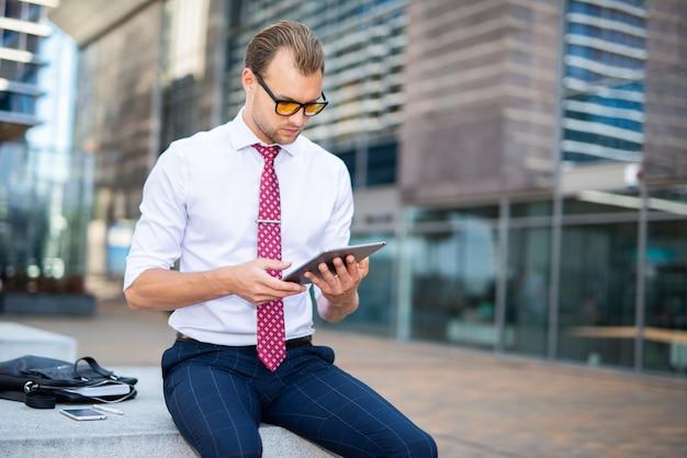 Uomo d'affari che utilizza una compressa digitale in un ambiente urbano