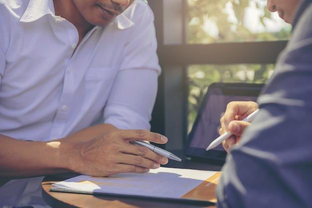 Uomo d'affari che usa il gesto della mano mentre spiega il rapporto aziendale e la discussione nella riunione