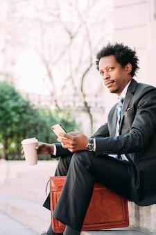 Uomo d'affari utilizzando il suo telefono cellulare e bere una tazza di caffè durante una pausa dal lavoro mentre è seduto all'aperto.