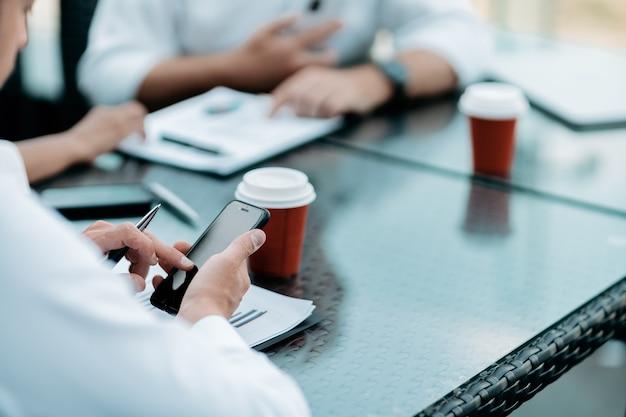 Uomo d'affari che usa il suo smartphone per analizzare un grafico finanziario