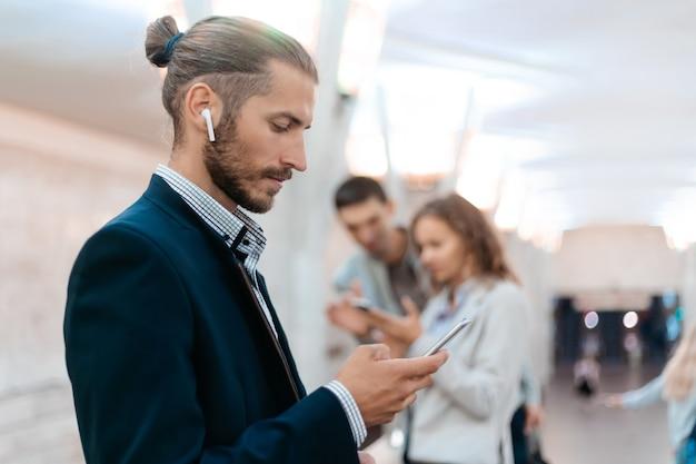 Uomo d'affari utilizzando il suo smartphone in metropolitana