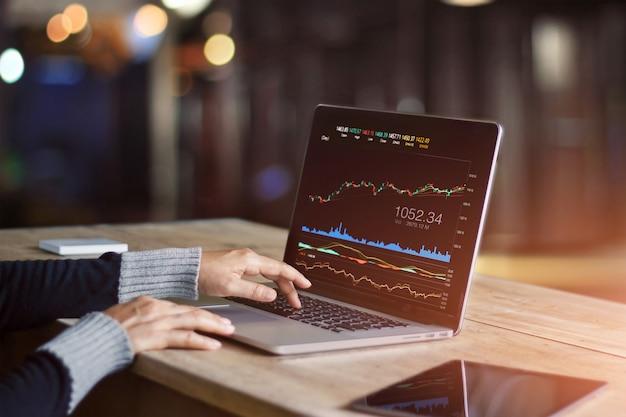 Uomo d'affari che per mezzo del computer portatile per analizzare il mercato azionario di dati
