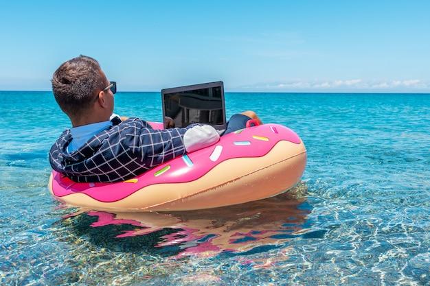 Uomo d'affari utilizzando il computer portatile su una ciambella gonfiabile in mare