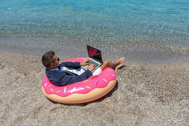 Uomo d'affari che per mezzo del computer portatile sulla ciambella gonfiabile sulla spiaggia tropicale