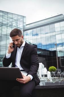 Uomo d'affari che per mezzo del computer portatile mentre parlando sul telefono