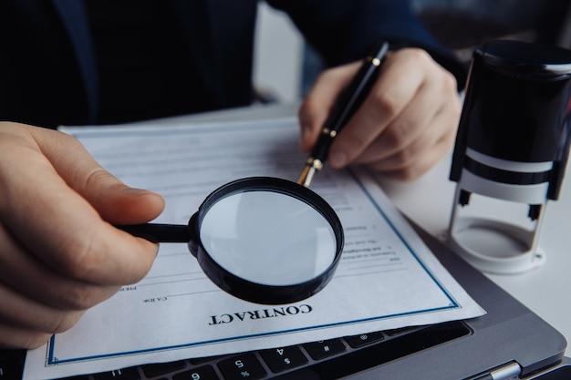 Uomo d'affari utilizzando la lente d'ingrandimento per approvare un contratto