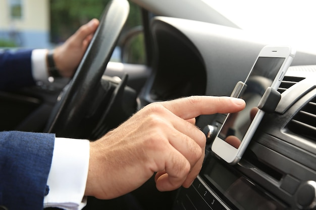 Uomo d'affari che utilizza il telefono cellulare per la navigazione durante la guida dell'auto, primo piano