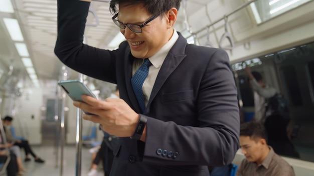 Uomo d'affari utilizzando il telefono cellulare sul treno pubblico. concetto di pendolarismo di stile di vita urbano della città.