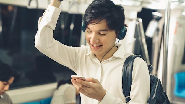 Uomo d'affari utilizzando il telefono cellulare sul treno pubblico