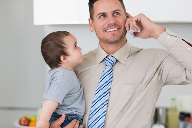 Uomo d'affari che utilizza telefono cellulare mentre portando bambino